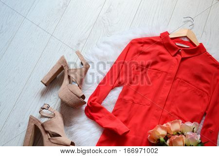 Fashion concept. Red blouse and beige shoes on a light wooden background. top view