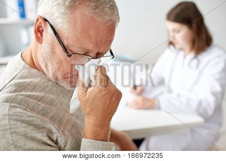 medicine, age, health care, flu and people concept - close up of senior man blowing nose with napkin and doctor at medical office at hospital