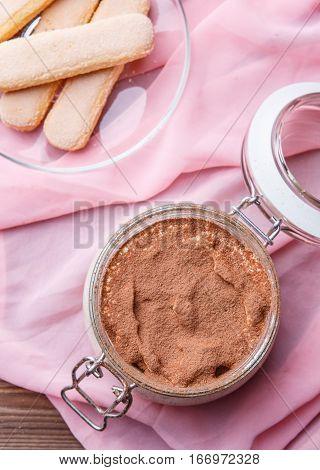 Tiramisu, cookies Savoiardi on pink tissue on brown wooden table