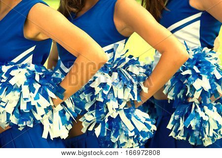 Cheerleaders in Uniform Holding Pom-Poms