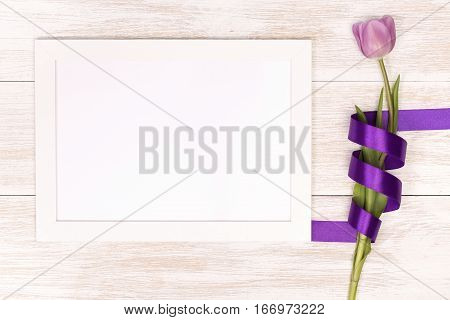 Lilac tulip and banner space for text in the white wooden table. Banner template layout mockup for Woman Day, Valentines Day and Teacher's Day. Photo for posts, blogs, advertising and news.