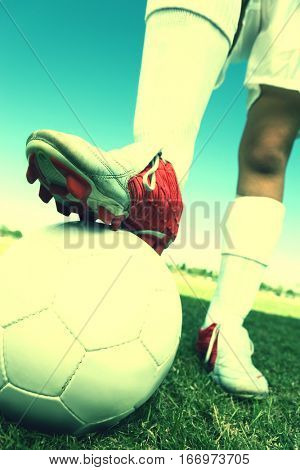Closeup low section of a soccer player with leg on ball