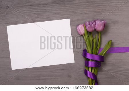 Lilac  tulips  in the lilac wooden table. Banner template layout mockup for Woman Day, Valentines Day and Teacher's Day. Photo for posts, blogs, advertising and news.