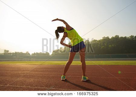 young fitness woman runner stretching on stadium track