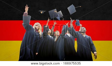 education, graduation and people concept - group of happy international students in bachelor gowns throwing mortarboards up over german flag background