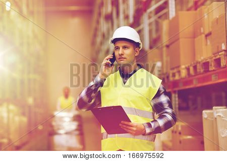wholesale, logistic, business, export and people concept - man in hardhat and reflective safety vest with clipboard calling on smartphone at warehouse