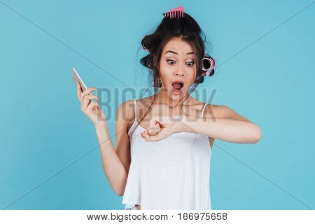 Picture of shocked young woman with hair curlers isolated over blue background using phone and look at imaginary watch