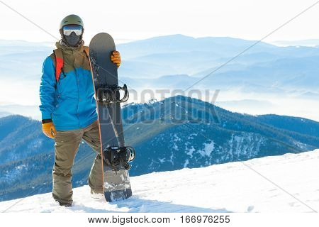 Young Snowboarder Standing Next To Snowboard Thrusted Into Snow With Beautiful Scenery On Background