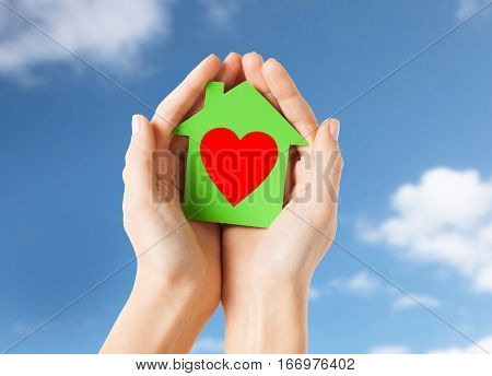 charity, real estate and love concept - close up of female hands holding green paper house with red heart shape