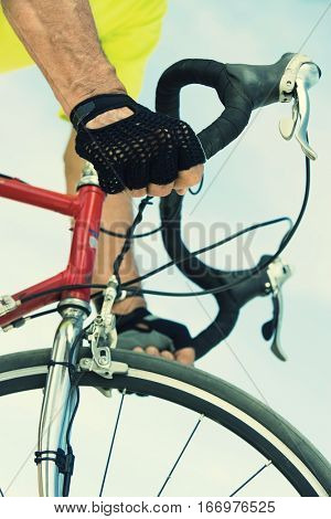 Cyclist holding handle bars on bicycle