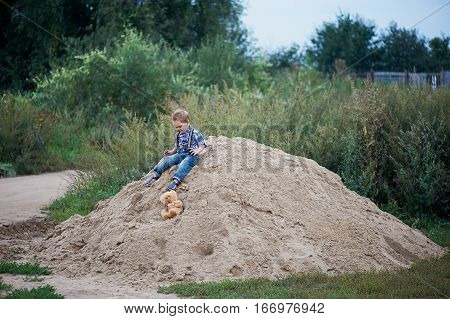 Little cute boy sitting on a big pile of sand, stylish jeans with suspenders and plaid shirt. Memories of childhood and carefree