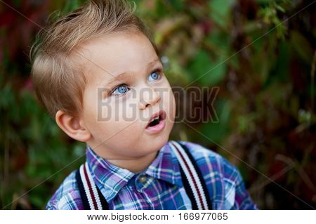 Portrait of cute little boy with big blue eyes and a stylish hairstyle, suspenders and a plaid shirt . Memories of childhood and carefree