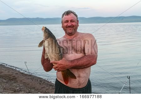 Siberian stocky man with fish. Khakassia, Russia poster