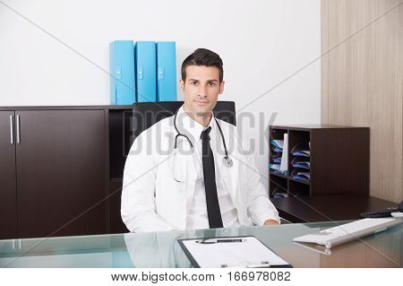 young male doctor showing pills in his studio
