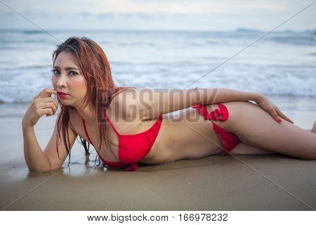 Beautiful asian woman in red bikini posing at beach