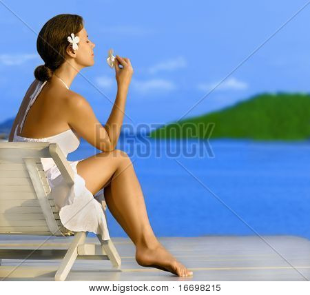 Woman  sitting on the chair near the ocean