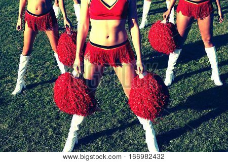 Low section of three cheerleaders in red costume with pom poms on field