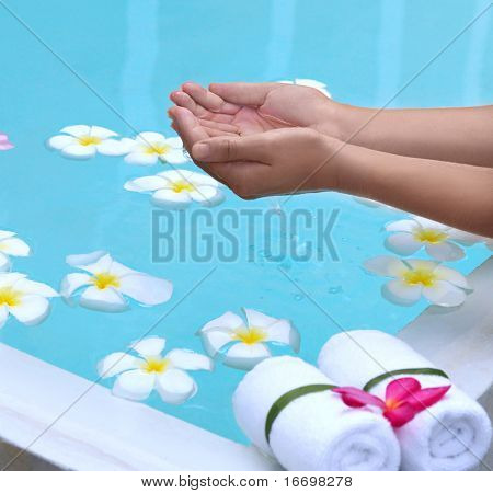 spa objecs with flowers towels and hands with water