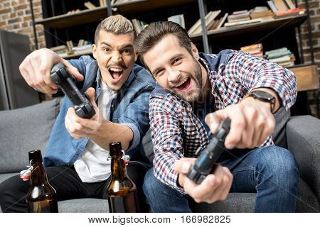 Young emotional men playing with joysticks on couch