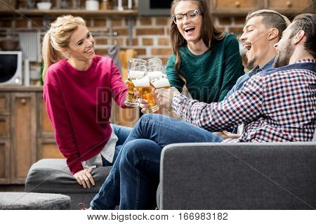 Happy young friends drinking beer and clinking glasses