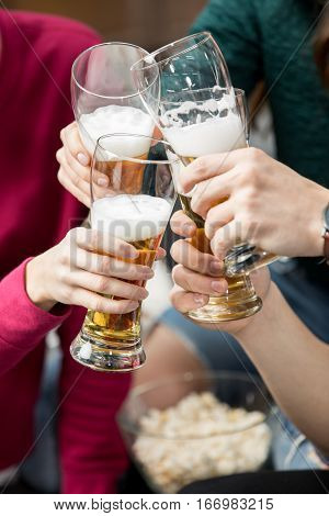 Close-up partial view of young friends clinking beer glasses