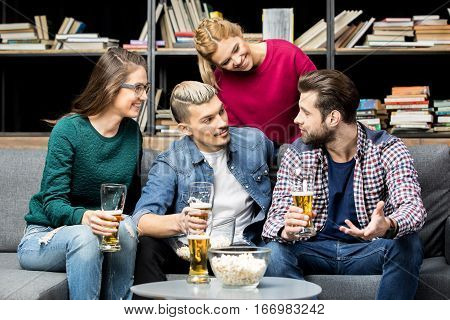 Male and female friends drinking beer and talking on couch
