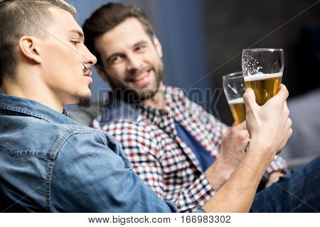 Two young male friends drinking beer at home