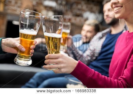 Close-up partial view of young friends drinking beer at home