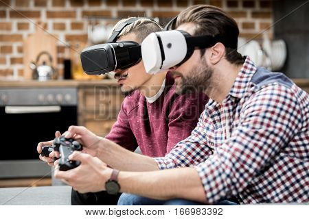 Male friends playing vigeo game in virtual reality glasses