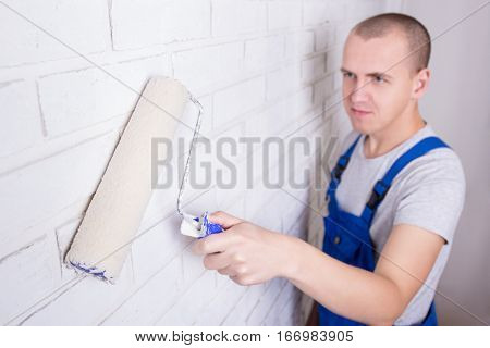 Young Man Painter In Workwear Painting Brick Wall With Paint Roller