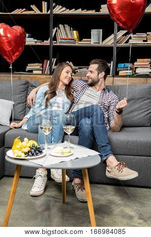 Couple holding heart shaped air balloons while sitting on sofa