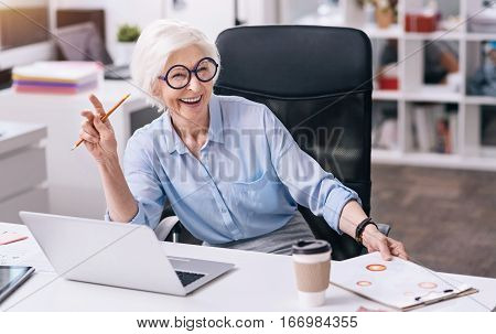 Positive atmosphere. Funny smiling aged businesswoman sitting at the table in the office in front of the laptop and holding the document table while expressing gladness