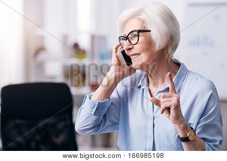 Involved in the conversation. Attentive smiling aged businesswoman standing in the office and holding the smartphone while enjoying conversation and showing the forefinger up