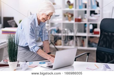 Using modern gadgets at work. Cheerful smiling aged businesswoman sitting on the table in the office and using the laptop while expressing happiness and working on the project