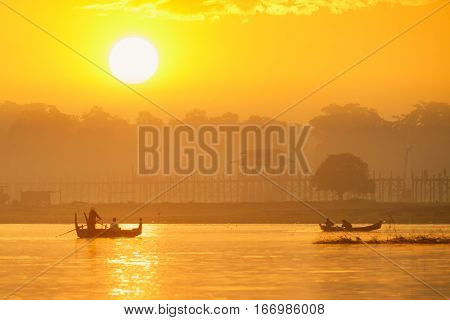 Unidentified ferryman row a boat for preparing to take tourists U Bein bridge Mandalay Myanmar
