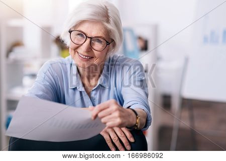 Enjoying my job . Happy involved aged woman sitting in the office and holding the papers while expressing positivity and working on the project