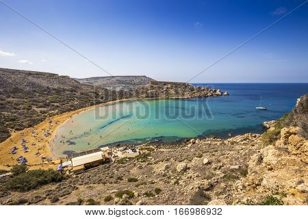 Ghajn Tuffieha Malta - Beautiful summer day at Ghajn Tuffieha sandy beach with blue sky and crystal clear green sea water