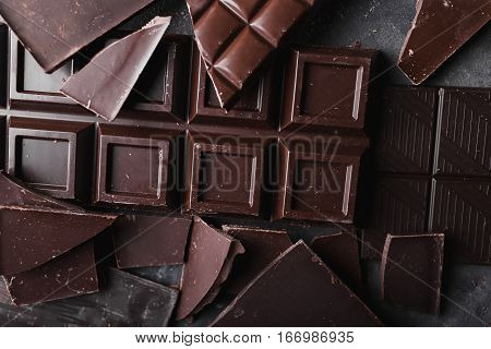 Chocolate chocolate chunks. Chocolate bar pieces. A large bar of chocolate on gray abstract background. Background with chocolate.