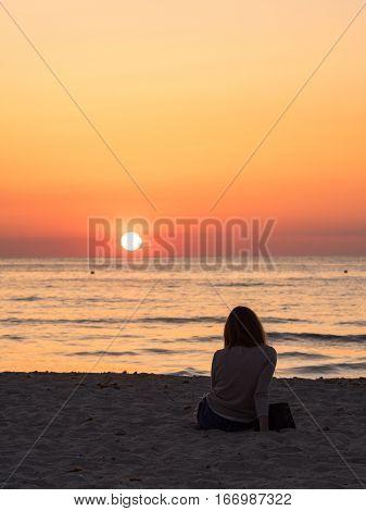 A Girl in Cala Saona beach in Formentera watching the sunset