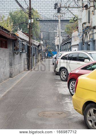 Beijing, China - Oct 30, 2016: Narrow Old Beijing streets or alleys are called Hutongs. Image features Cuihua Hutong, typically made narrower by parked cars.