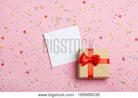A gift in kraft box with a red bow and paper for notes on a pink background with decorations. Surprise your loved one. The concept of the day of St. Valentine's, weddings, engagements, Mother's Day, birthday, New Year, Christmas and other holidays. Flat f