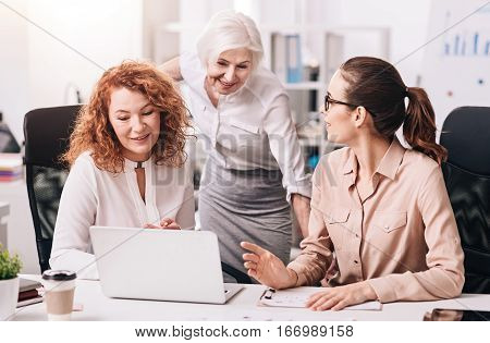 In touch with everyone . Involved pleasant lively colleagues sitting in the business center and using the laptop while sharing points of view and expressing positivity