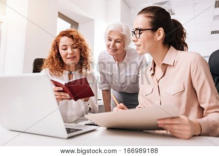 Discussing every detail. Involved glad lively colleagues sitting in the office and using the laptop and papers while sharing points of view and expressing positivity