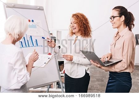 Discussing statistics. Glad involved cheerful coworkers expressing happiness and standing in the office in front of the white board while working and sharing ideas