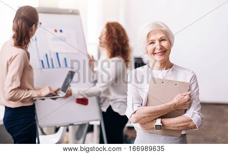 Feeling pride for my company . Glad positive aged businesswoman standing in the office and holding the clipboard while her colleagues working in the background
