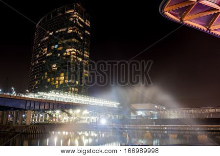 Tall iluminated skyscraper in a wharf at night