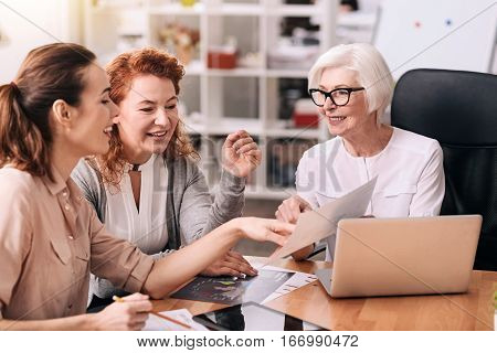 Involved in the discussion. Smiling positive involved businesswomen sitting in the office in front of the laptop and using the documents while exchanging opinions