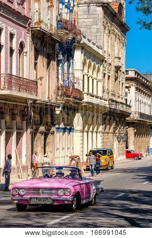 HAVANA,CUBA - JANUARY 24,2017 : A classic convertible car drives tourists around Old Havana  on a street sidelined by colorful buildings