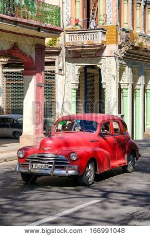 HAVANA,CUBA - JANUARY 24,2017 : A classic red Chevrolet in Old Havana  on a street sidelined by colorful buildings