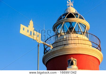 The weathercock of the lighthouse of Salou in the rays of the rising sun. Salou. Spain.